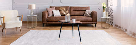 Panoramic view of elegant living room with brown leather sofa, armchair and coffee table, real photo