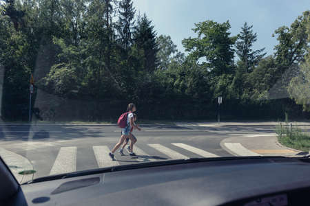 Two school kids on the pedestrian crossing, view from inside the car Stock Photo