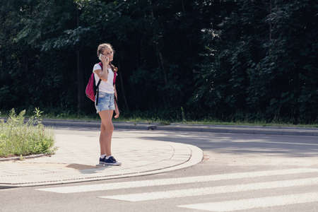 Teenager schoolgirl talking on the phone and walking in pedestrians crossing
