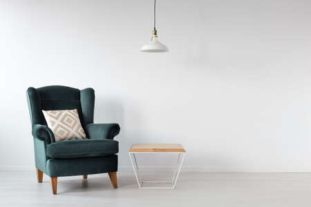 Moss green armchair next to wooden coffee table in white scandinavian interior with copy space on the empty wall 写真素材