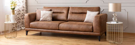 Panoramic view of brown leather sofa between two stylish tables with marble tops, real photo