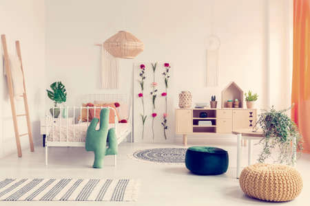 Boho kids bedroom with white metal bed, wooden furniture and colorful poufs, real photo