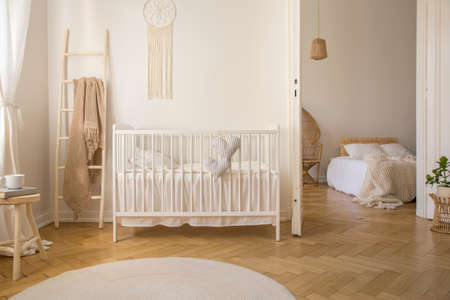 Wooden ladder with beige blanket on it, next to white crib with pillows, real photo