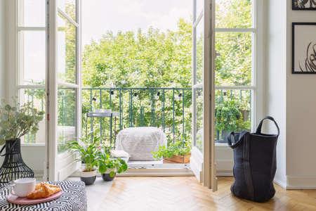 Plantas verdes en macetas en puerta abierta al balcón con pequeña mesa elegante y puf, foto real Foto de archivo