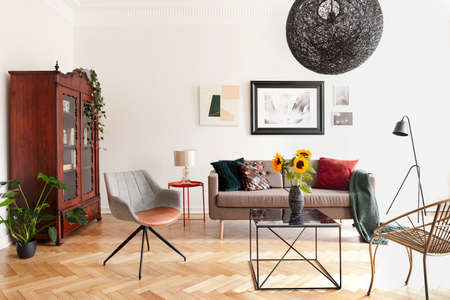 Sunflowers on table between armchairs in white flat interior with posters above sofa. Real photo Imagens
