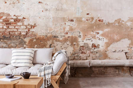 Wooden table in front of beige sofa with cushion and blanket in minimal flat interior. Real photo Stock Photo