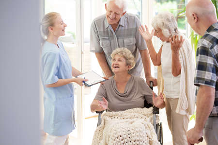 Smiling nurse talking with happy senior woman in the wheelchair and elderly people
