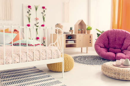 Stylish amaranth armchair in elegant girl's boho bedroom interior with flowers and wooden furniture Stok Fotoğraf - 110949042
