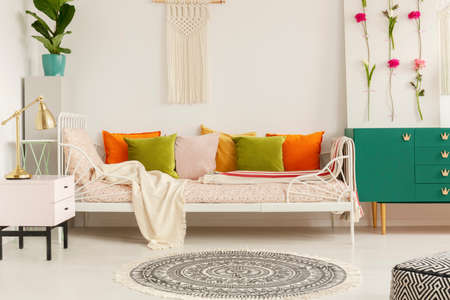 Olive green, orange, yellow and pastel pink pillows on comfortable bed in boho bedroom of stylish apartment, real photo