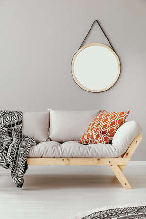 Mirror above scandinavian settee with patterned pillow and blanket Stock Photo