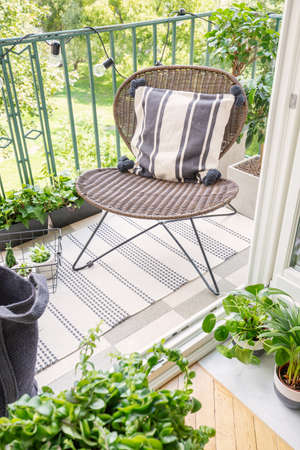 Top view of stylish rattan chair with patterned pillow on the balcony of modern flat, real photo Фото со стока
