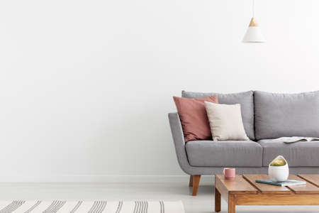 Pillows on grey settee and wooden table in white apartment interior with copy space on the wall. Real photo