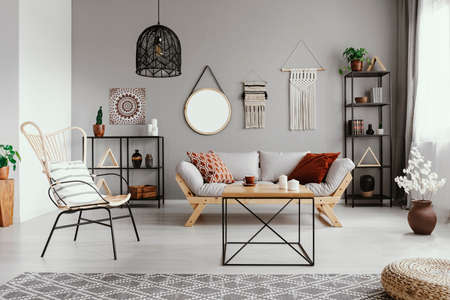Mirror, macrame and graphic on the grey wall of warm ethno living room with stylish furniture and cozy patterned carpet Stock Photo - 110977226