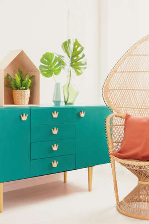 Green cabinet with stylish crown shape handles next to peacock chair with orange pillow, real photo Stock Photo