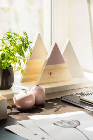 Pink vases, plant and triangles on window sill in workspace interior with drawings on desk. Real photo