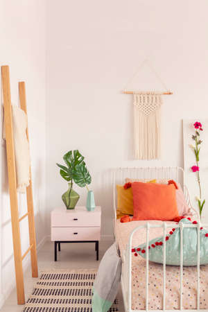 Orange pillow on single metal bed in stylish bedroom interior with pink bedside table and white macrame on the wall Stok Fotoğraf - 110977315