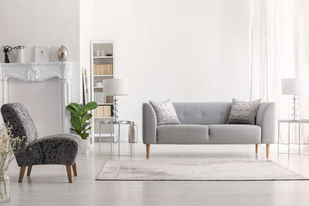 Carpet near armchair and grey settee in white living room interior with lamp on table. Real photo
