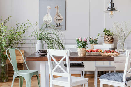Rustic dining room with long table and white chairs and oil painting on the grey wall, real photo Stock Photo