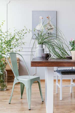 Vista vertical de la silla verde menta junto a la mesa de madera con jarrón con planta verde y taza de café grande, pintura al óleo rústica en la pared