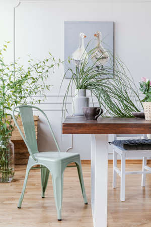 Vue verticale d'une chaise vert menthe à côté d'une table en bois avec un vase avec une plante verte et une grande tasse à café, peinture à l'huile rustique sur le mur
