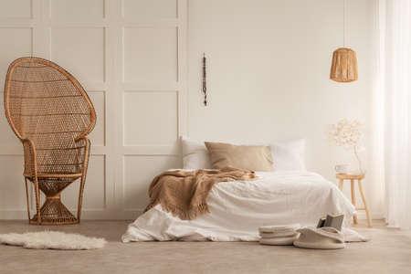 Elegante silla de pavo real en un elegante dormitorio creado con materiales naturales, foto real con espacio de copia en la pared vacía