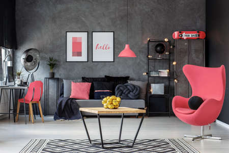 Rogue pink egg chair in dark scandinavian living room with home office and coffee table, real photo 版權商用圖片