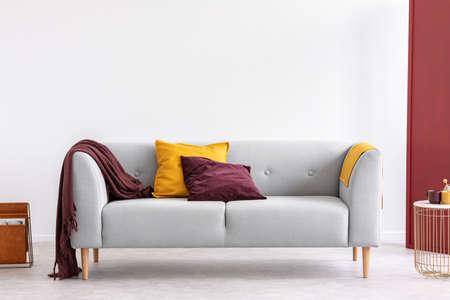 Burgunder Kissen und Decke und gelbes Kissen und Decke auf stilvoller grauer Couch im eleganten Wohnzimmer mit Kopienraum an der weißen leeren Wand