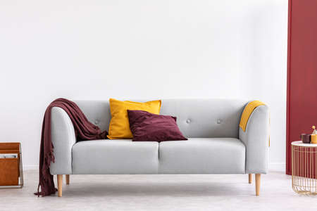Burgundy pillow and blanket and yellow pillow and blanket on stylish grey couch in elegant living room interior with copy space on the white empty wall