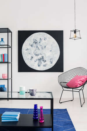 Vertical view of moon graphic on the wall of stylish white living room interior th trendy armchair, real photo