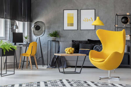 Industrial lamp in the corner of spacious scandinavian living room with yellow egg char, home office and coffee table with basket full of lemons, real photo