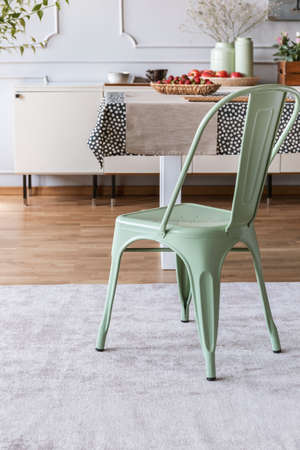 Mint green chair on grey carpet at table in rustic dining room interior with lamp and wall with molding. Real photo Foto de archivo - 110973447