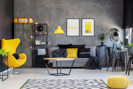 Yellow egg chair in modern living room interior with home office and comfortable sofa with pillows, real photo with posters on concrete wall
