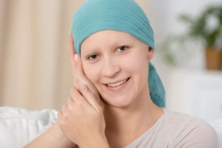 Close-up of a woman with cancer smiling and being touched by someone