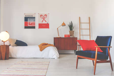 Red pillow on blue armchair in white bedroom interior with wooden cabinet next to bed. Real photo