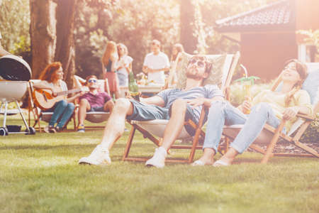 Young people relaxing on sunbeds in the park during summer