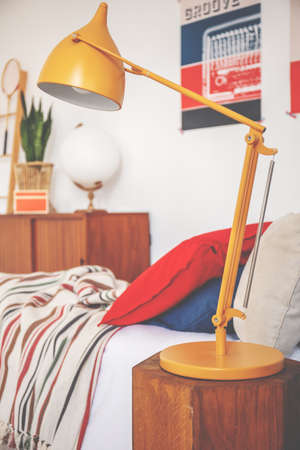 Yellow lamp on wooden stool next to bed with red pillow in teenagers bedroom interior. Real photo Stock Photo