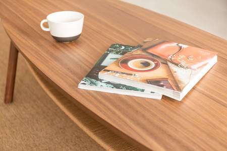 Two magazines and empty coffee mug on the wooden table, real photo