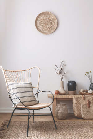 Wicker chair with striped pillow on it next to wooden table full of accessories such as vase, flowers and candles