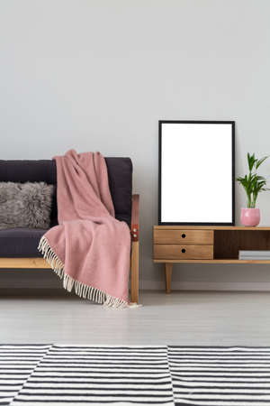 Vertical view of sofa with pastel pink blanket next to wooden cabinet with mockup poster in back frame