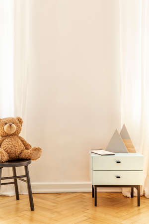 Real photo of an empty wall in a kid room interior with a teddy bear and cabinet with decorative triangles