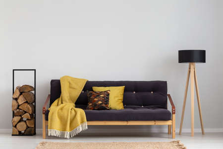 Log of wood next to comfortable sofa with yellow blanket and pillows, stylish wooden lamp with black lampshade, real photo copy space on the empty grey wall Stockfoto