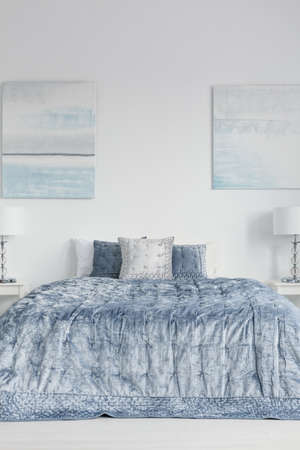 Posters on white wall above bed with blue sheets and cushions in bedroom interior with lamps. Real photo