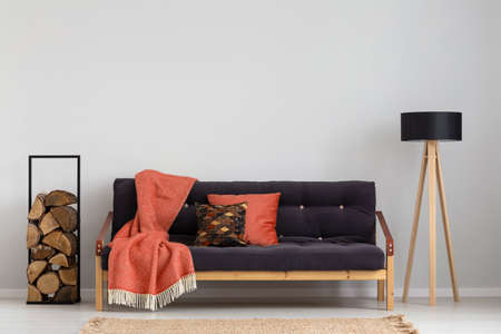 Log of wood next to comfortable sofa with strawberry red blanket and pillows, stylish wooden lamp with black lampshade, real photo copy space on the empty grey wall Stockfoto - 111119991