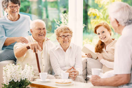 Happy elderly people drinking tea in the common room of nursing house Reklamní fotografie