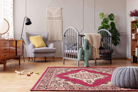 Rustic rug in stylish baby bedroom with grey and vintage furniture, real photo with copy space