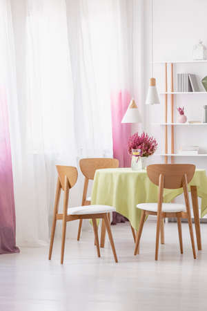 Table with lemon water, fresh heather and green tablecloth in real photo of dining room interior with lamps, window with curtains and rack with decor and books Фото со стока