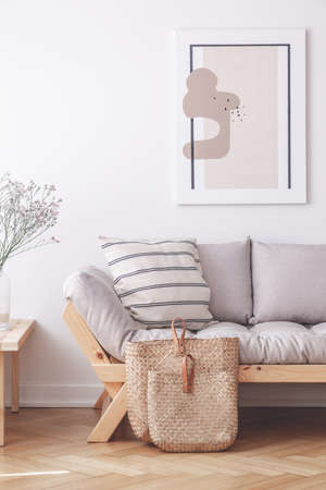 Two bags on the floor of stylish apartment with grey couch and framed print on the wall