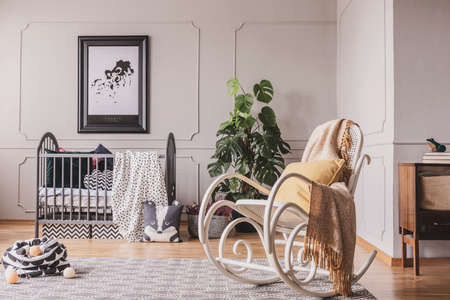 Rocking chair with blanket and pillow in stylish baby room interior with grey crib, map on the wall and patterned rug on the floor, real photo