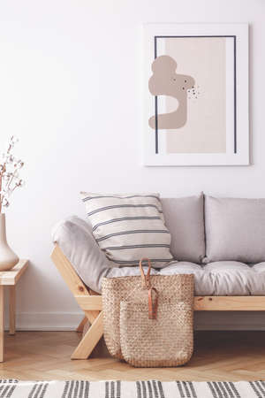 Abstract painting on the wall of natural beige living room with grey settee in lagom inspired interior Stock Photo