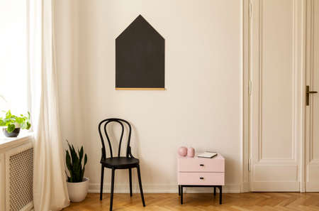 Real photo of a living room interior with a chair, cabinet and house shaped blackboard on the wall Stock Photo